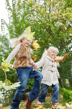 romp: Two little girls playing with autumn leaves at the park