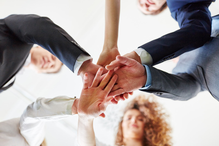 Group of business people as team putting hands together as motivation Banque d'images