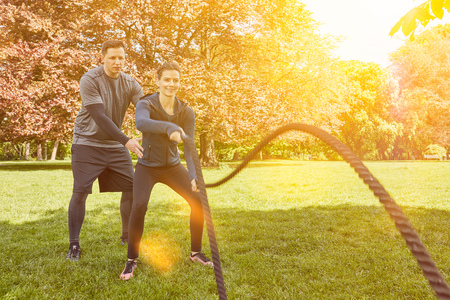 Woman in battle rope fitness training with Personal Trainer