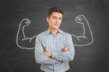 Strong and self confident businessman with chalk muscles on blackboard behind him photo