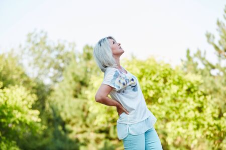 Senior woman having lumbago pain in the nature in summer Stock Photo