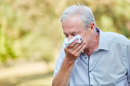 miffed: Old man with a cold using a tissue in the nature