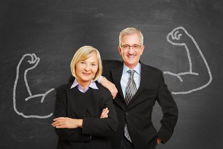 Business team with chalk muscles on blackboard as strength and success concept photo