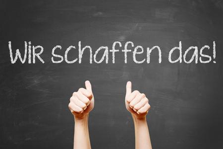 """Niemiecki slogan """"Wir schaffen das"""" (możemy to zrobić) z kciukiem do góry na tablicy"""