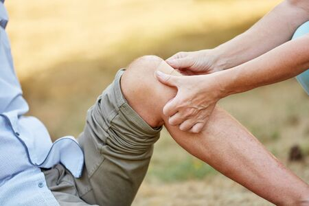 Woman puts a bandage on an injured knee and helps the man Stock Photo