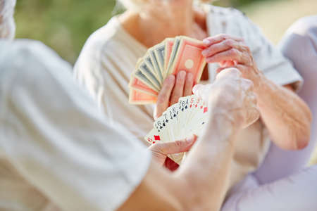 play the old park: Two retired seniors playing cards as a hobby in the garden in summer