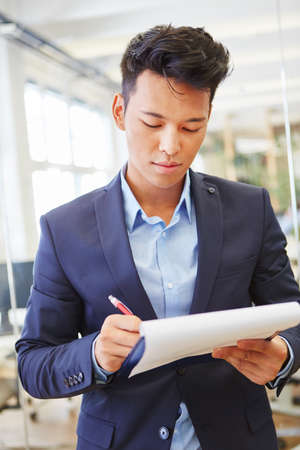 Consultant writing on his checklist and controls business plan Stock Photo
