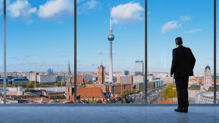 Business man looking onto Berlin city with TV tower and town hall
