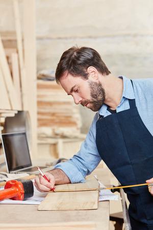 De timmerman meet hout met nauwkeurigheid op workshop
