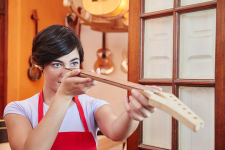 Woman controls quality of handmade fingerboard for guitar Stock Photo