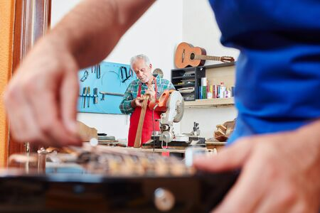 Luthier repairing guitar while collegue repairs electric guitar Stock Photo