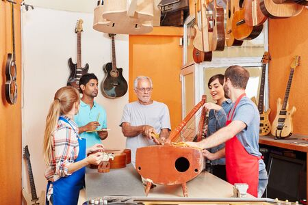Guitar making at luthiers workshop with artisans team Stock Photo