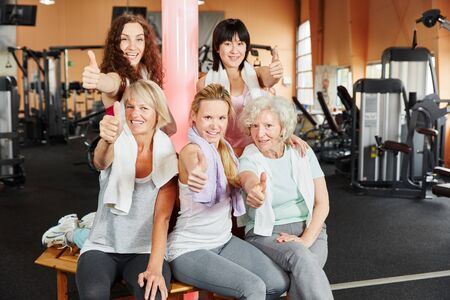 Young and senior women holding thumbs up as a group at the gym photo