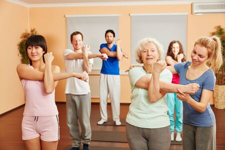 Trainer helps senior woman with yoga exercise at a fitness center photo
