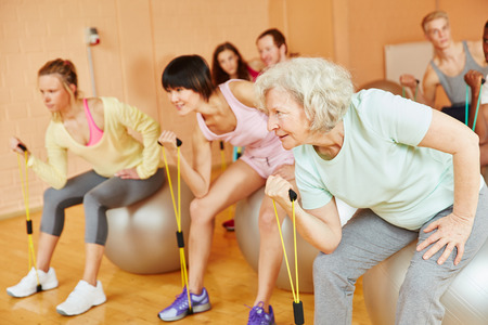 Senior making exercise with expanding band during pilates at the gym photo