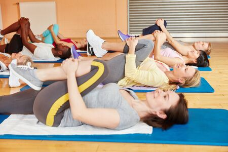 Women making stretching exercise during pilates class at fitness center photo
