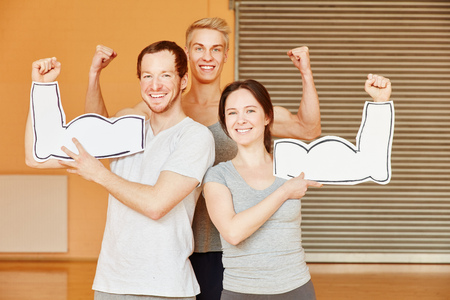 Successful friends showing muscles at fitness studio Stock Photo