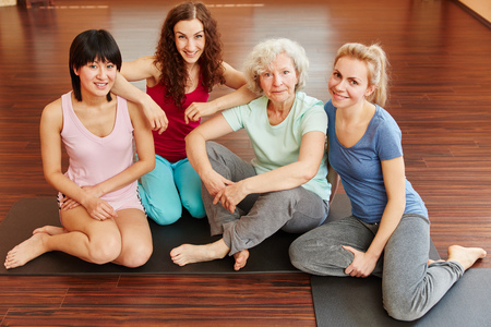 Sporty senior citizen and young women in yoga class photo