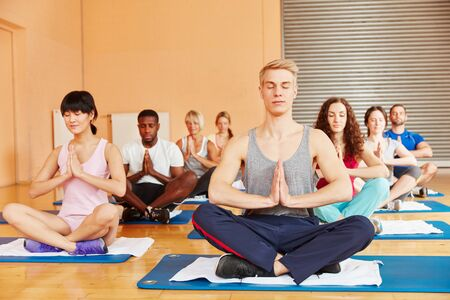 Group in yoga class meditating together at health club photo