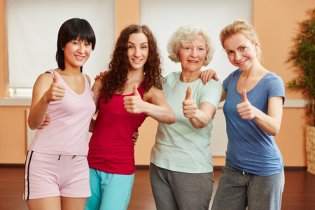 Group of women holding thumbs up at fitness center photo