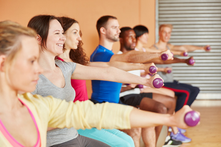 People training with weights in fitness class at the gym photo