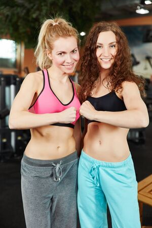 Two sporty women clentching their fists at the gym photo