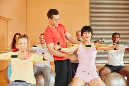 Fitness trainer shows exercise with band during rehab class photo