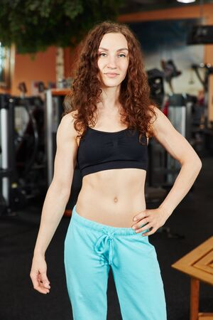 Sporty woman at the gym standing confidently photo