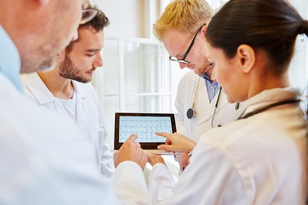 associate: ECG Diagnostic with tablet computer and group of doctors Stock Photo