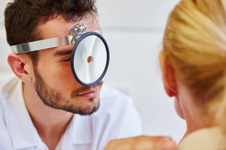 ent: ENT specialist examinating patient with front reflector