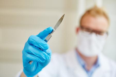 Arts als chirurg met scalpel en handschoenen tijdens de operatie