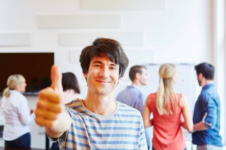 Happy young man holding thumbs up in front of his business team Stock Photo