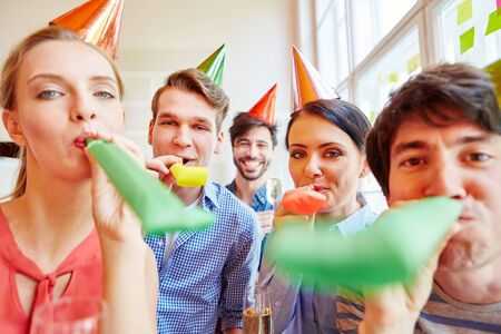 Group of young people having fun with noisemakers in party