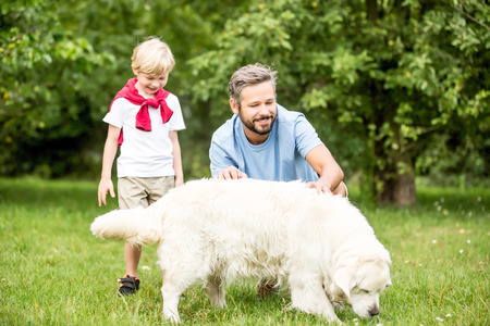 Father and son with dog Retriever togheter in summer at garden