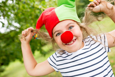 Girl in clown costume with red nose having fun in carnival