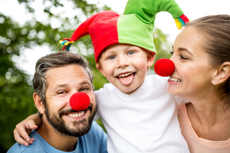 Happy boy wearing fool cap with parents in carnival
