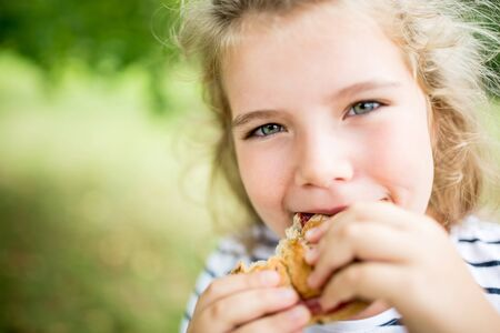 Girl eating snack bun at the park in summer out of hunger