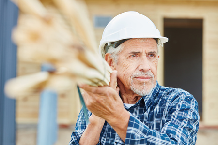 Senior craftsman working at construction site carrying wood Stock Photo