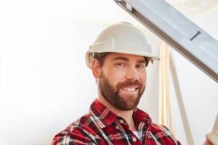 Skilled window builder mechanic fitting new window at construction site Stock Photo