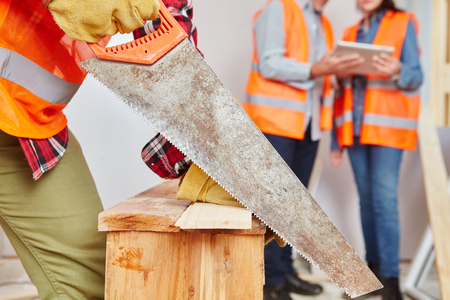 Craftsman with hand saw cutting wood at construction site Stock Photo
