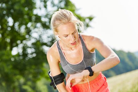 Woman controls her vital signs with smartwatch after jogging Foto de archivo