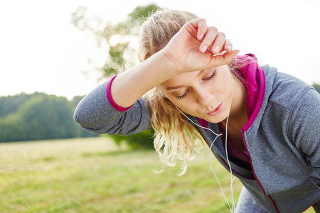 Exhausted woman after jogging catching her breath