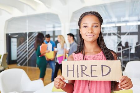 African woman holding sign with word hired at start-up office Stock Photo