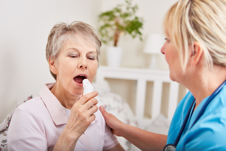 Ltere Frau erhält erste Hilfe von der Krankenschwester und benutzt Inhalator Standard-Bild - 82062651