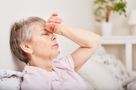Ill senior woman with headhache lie in bett Stock Photo