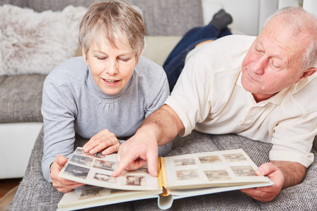 photo album: Senior couple in relaxation holding photo album