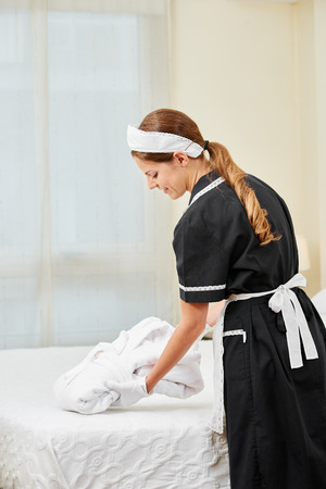 Maid bringing fresh bathrobe in hotel room during housekeeping Stock Photo