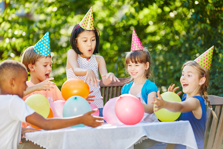 Kids have fun at childrens birthday party in summer in garden Stockfoto