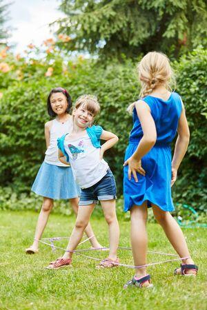 saltar: Tres niñas juegan como amigos chino saltar la cuerda en el jardín con banda de goma