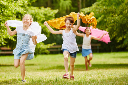 Children running in freedom in the park holding cloths in the air Stok Fotoğraf